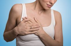 Cropped portrait young woman with breast pain touching chest Royalty Free Stock Images