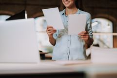 Charming girl holding two blank paper cards and smiling royalty free stock photography