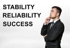 Cropped portret biznesmena główkowanie z x27 &; stabilność, niezawodność, success& x27; słowa obok on Obrazy Stock