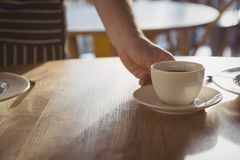 Cropped ręka kelner porci kawa na stole Fotografia Royalty Free