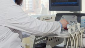 Cropped rear view shot of a male doctor using ultrasound scanner stock video footage