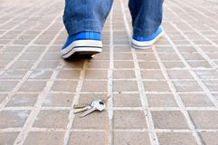 Losing my keys. Cropped rear view of a walking young who loses the home keys on the sidewalk street in the city royalty free stock photo