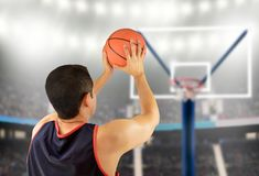 Basketball player in free throw pose. Cropped rearview of a basketball player taking free throw against at stadium stock image