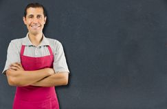 I am willing to help you. Cropped of shopman with arms crossed and smiling  over a blackboard background with copyspace Stock Photo