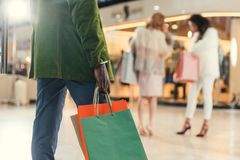 Cropped shot of african american man holding paper bags while walking in shopping mall Royalty Free Stock Images