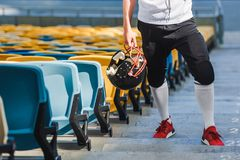 Cropped shot of american football player with helmet standing on stairs. At sports stadium Stock Image