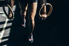 Woman exercizing with gymnastic rings. Cropped shot of athletic sportswoman doing exercises with gymnastic rings at gym royalty free stock photography