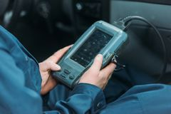 Automechanic using car diagnostic tool. Cropped shot of automechanic using a car diagnostic tool in a service workshop royalty free stock photos