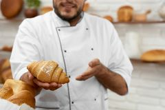 Young man working at his bakery. Cropped shot of a baker offering you delicious aromatic freshly baked croissant posing at his store copyspace pastry bakery food Royalty Free Stock Photo