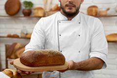 Young man working at his bakery. Cropped shot of a baker in uniform holding a loaf of bread posing at his bakery seller selling retail salesperson small business Stock Photo