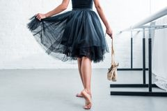 Cropped shot of ballerina in black tutu holding pointe shoes in ballet studio stock photography
