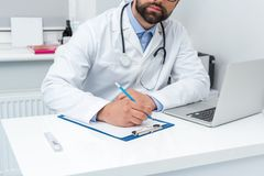 Cropped shot of bearded doctor writing. In clipboard Royalty Free Stock Photography