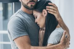 Cropped shot of bearded man. Hugging and supporting young sad woman stock images