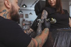 Young attractive woman getting new tattoo by professional tattooist. Cropped shot of a beautiful women getting her arm tattooed by professional tattoo artist royalty free stock image