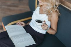 cropped shot blonde middle aged woman cropped shot blonde middle aged woman drinking coffee reading book cafe 119754980
