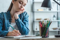 cropped shot of bored girl writing in notebook and studying stock photos
