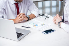 Cropped shot of business people sitting at table with charts, laptop and smartphone Royalty Free Stock Image