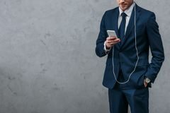 Cropped shot of businessman listening music with headphones. And smartphone stock images