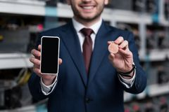 cropped shot of businessman showing smartphone and bitcoin at cryptocurrency stock images