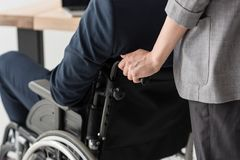 cropped shot of businesswoman helping disabled colleague stock photo