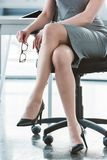 cropped shot of businesswoman in high heeled shoes sitting on chair royalty free stock photos
