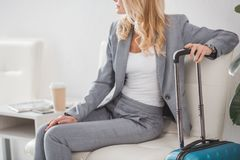 Businesswoman with luggage and coffee to go Stock Image