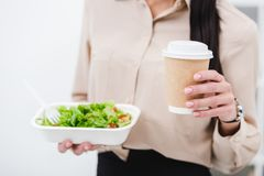 Cropped shot of businesswoman with take away food and coffee to go. In office stock photo