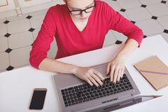 Cropped shot of busy female freelancer works remotely at home, keyboards something on portable laptop computer, surrounded with sm royalty free stock photo