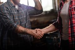 Cropped shot of carpenter with tattooed hand shaking hand of partner. At sawmill royalty free stock photography
