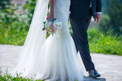 Cropped shot of Caucasian bride and groom walking together stock photo