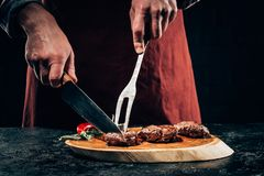 Chef in apron with meat fork and knife slicing gourmet grilled steaks with rosemary and chili pepper on wooden board. Cropped shot of chef in apron with meat stock photo