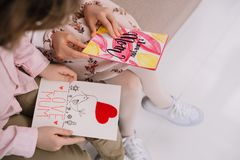 Cropped shot of children with mothers day greeting cards sitting on couch. At home royalty free stock image