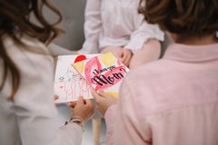 Cropped shot of children presenting mothers day greeting card. For mother stock photo