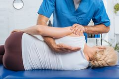 cropped shot of chiropractor massaging back of patient that lying on massage table