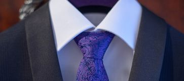 Cropped shot of classy navy blue suit with white shirt and embroidered silk necktie in Windsor knot. Male accessories for formal attire, fashion and beauty Royalty Free Stock Image