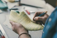 Cropped shot of cobbler holding pencil and working with unfinished footwear. Workpiece stock photo