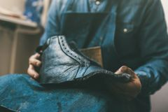 Cropped shot of cobbler holding unfinished leather shoe. At workshop royalty free stock photo