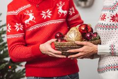 Couple holding baubles. Cropped shot of couple in knitted sweaters holding shiny baubles Royalty Free Stock Images