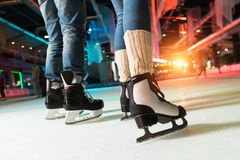Cropped shot of couple in skates ice skating. On rink royalty free stock photos