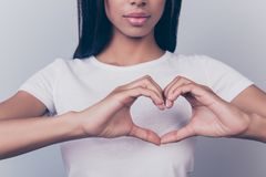 Cropped shot of cute brunette standing and showing heart gesture stock photos