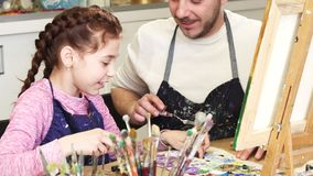 Cropped shot of a cute little girl smiling talking to her dad mixing paints at art class. Close up of a little adorable girl smiling cheerfully mixing oil paints stock photos