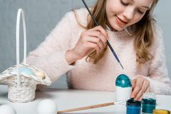 Cute smiling girl painting easter egg. Cropped shot of cute smiling girl painting easter egg royalty free stock photography