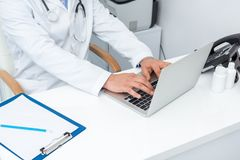 Cropped shot of doctor using laptop. At workplace Royalty Free Stock Image