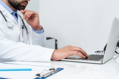 Cropped shot of doctor using laptop. At workplace Royalty Free Stock Photo