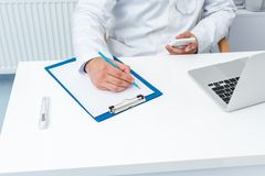 Cropped shot of doctor using smartphone and writing. In clipboard Stock Photos