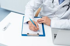 Cropped shot of doctor writing in clipboard. At workplace Stock Photography