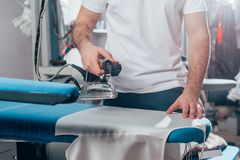 Cropped shot of dry cleaning worker using industrial iron. At warehouse royalty free stock image