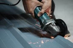 Cropped shot of Electric grinder Worker cutting. Stock Photo