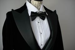 Elegant black tie suit with white shirt and silk bow tie on mannequin torso or a dress form. Cropped shot of elegant black tie suit with white shirt and silk bow stock photos