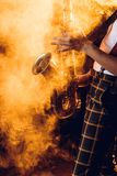 Cropped shot of expressive young musician playing saxophone. In smoke stock images